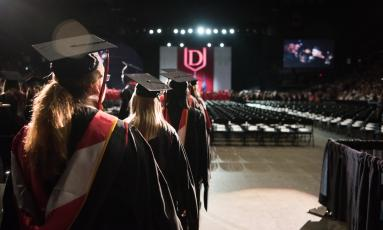 group of female students in graduation robes and mortarboards, walking into auditorium