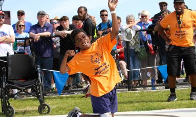 Boy winding up to throw shotput in front of a crowd