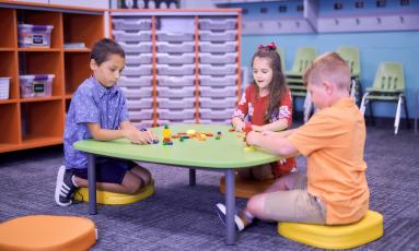 Children sitting at a low table stacking blocks